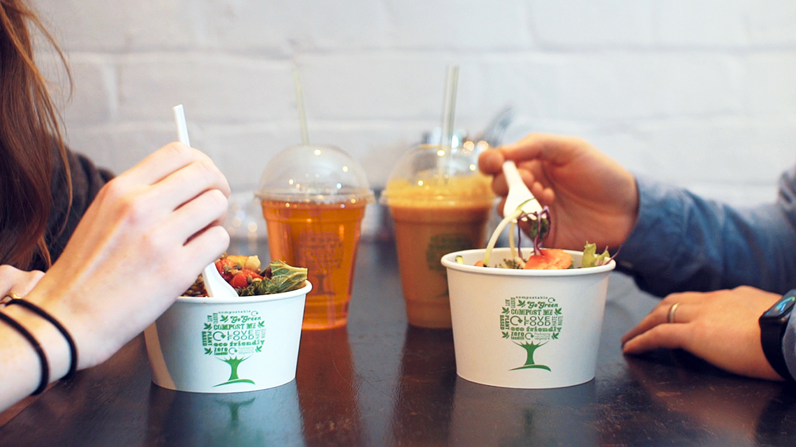 Two people enjoying lunch from Vegware plant-based foodservice disposables